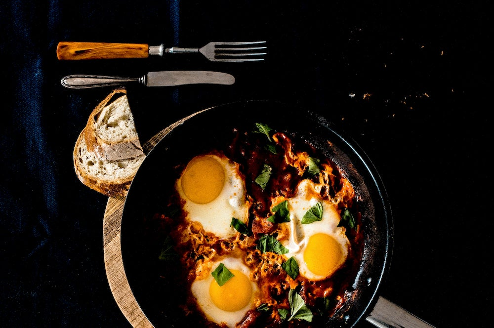 Silverware and bread surround a cast iron skillet full of eggs
