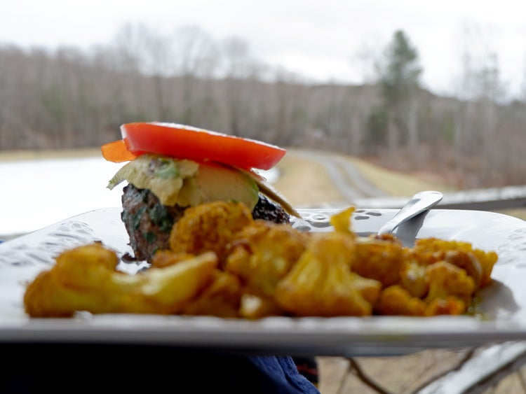 a camping meal of a burger and vegetables