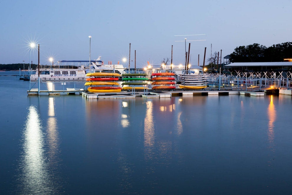 a marina holding boats and kayaks at night on the shore of a lake in texas
