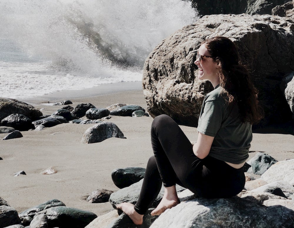 Girl sitting on rocky beach as surf breaks in the distance