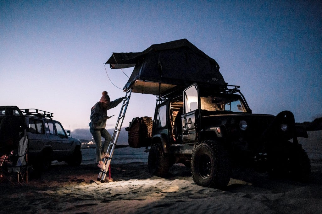 Man walking up ladder to camping car rooftop tent on the beach after dusk.