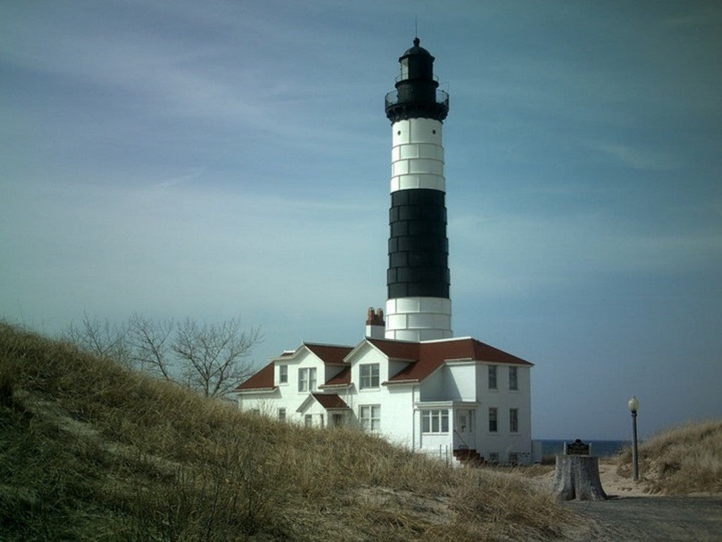 a black and white lighthouse hidden behind a sand dune near the beach in michigan