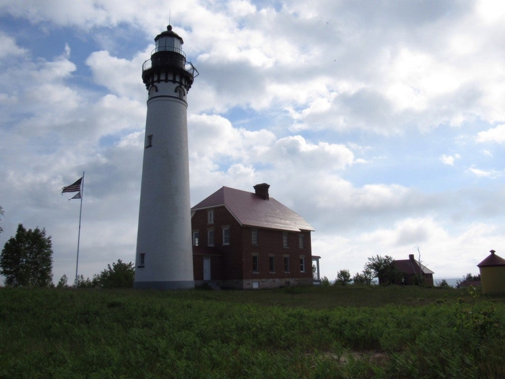 the au sable lighthouse next to a house in western michigan