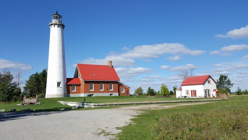a lighthouse in tawas point near two red buildings
