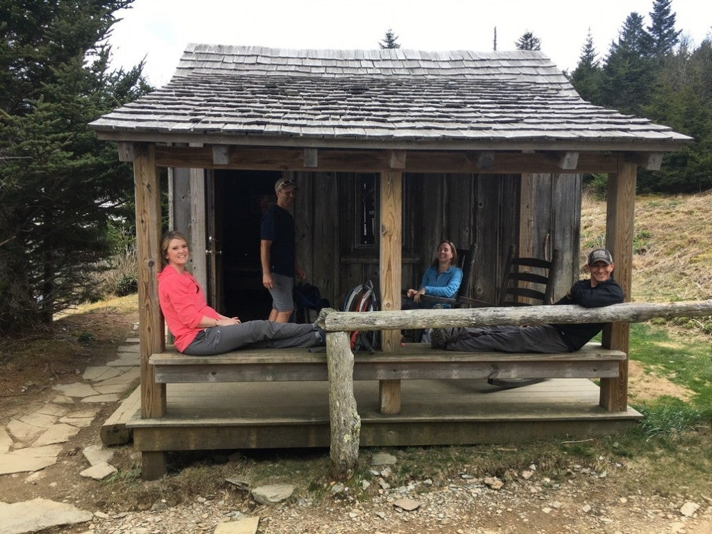 a group of people posing in front of a shelter at mount leconte lodge