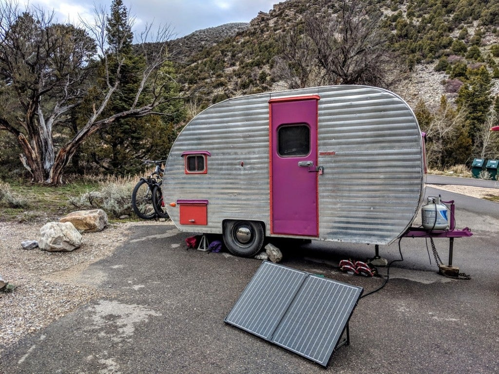 a solar panel connected to a tow trailer at a campsite