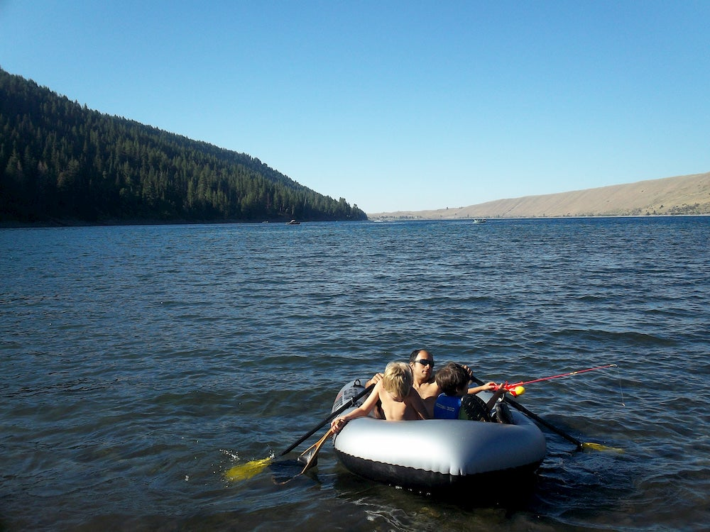man, accompanied by two children, paddles an inflatable boat on large lake