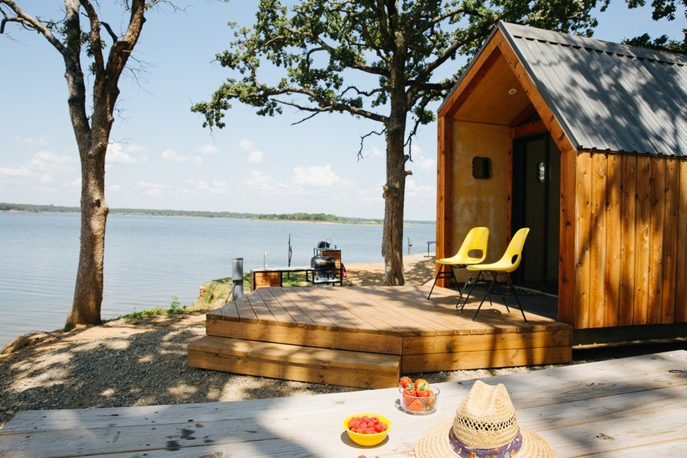 a wooden cabin built on the shore of a large lake in texas