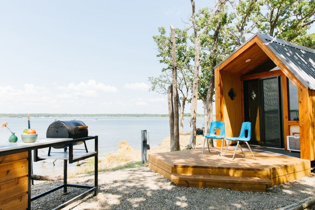 a wooden cabin with chairs on a porch in front of a lake in texas