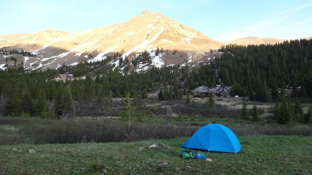 a blue tent set up in the shadown of a snowy mountain in colorado