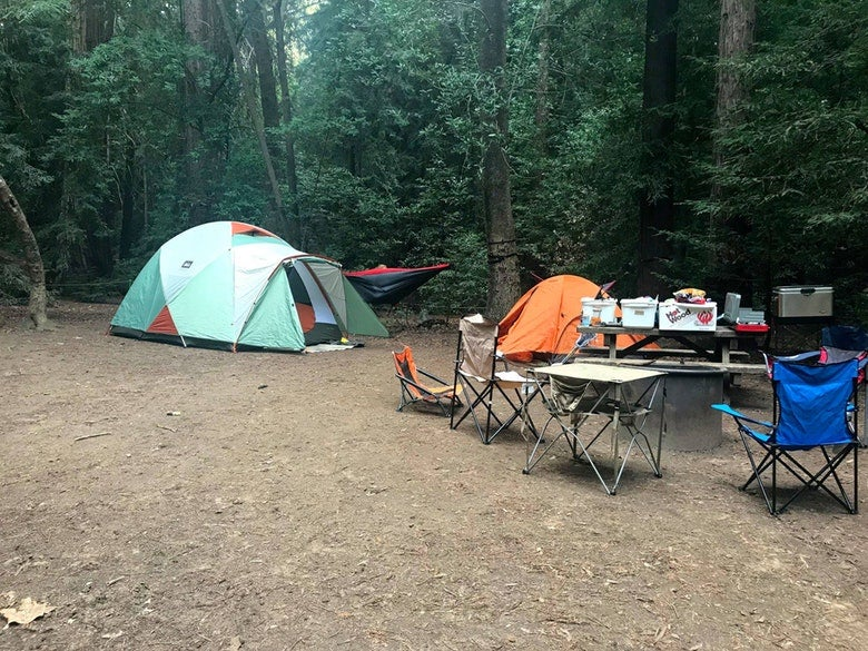 two tents, picnic chairs and a table are set up at a campground