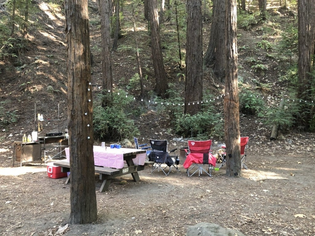 a campsite with a camping kitchen, picnic table and string lights at a campground in big sur