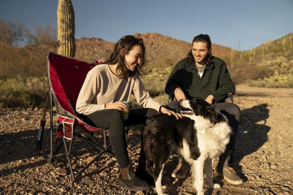 Couple sitting in camp chairs in the desert petting a dog.