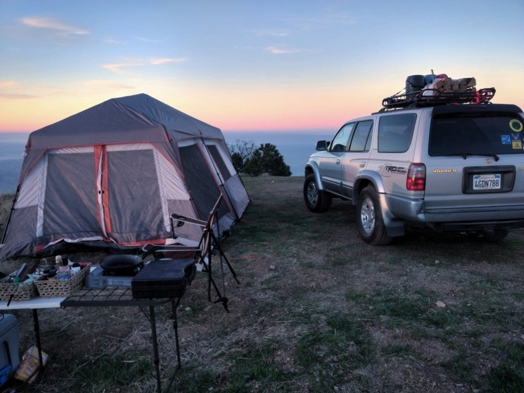 a tent and car set up at a campsite overlooking the ocean in big sur ca