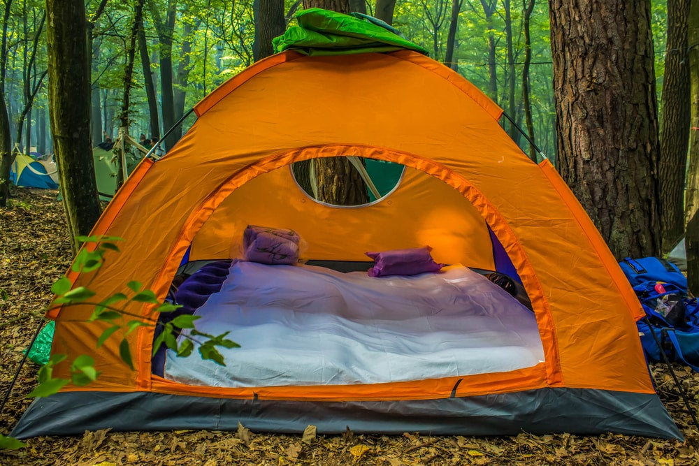 a tent in the woods with a mattress set up inside it