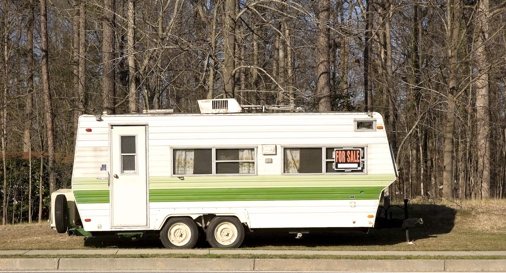 a towable camper trailer on the side of a road with a for sale sign on it