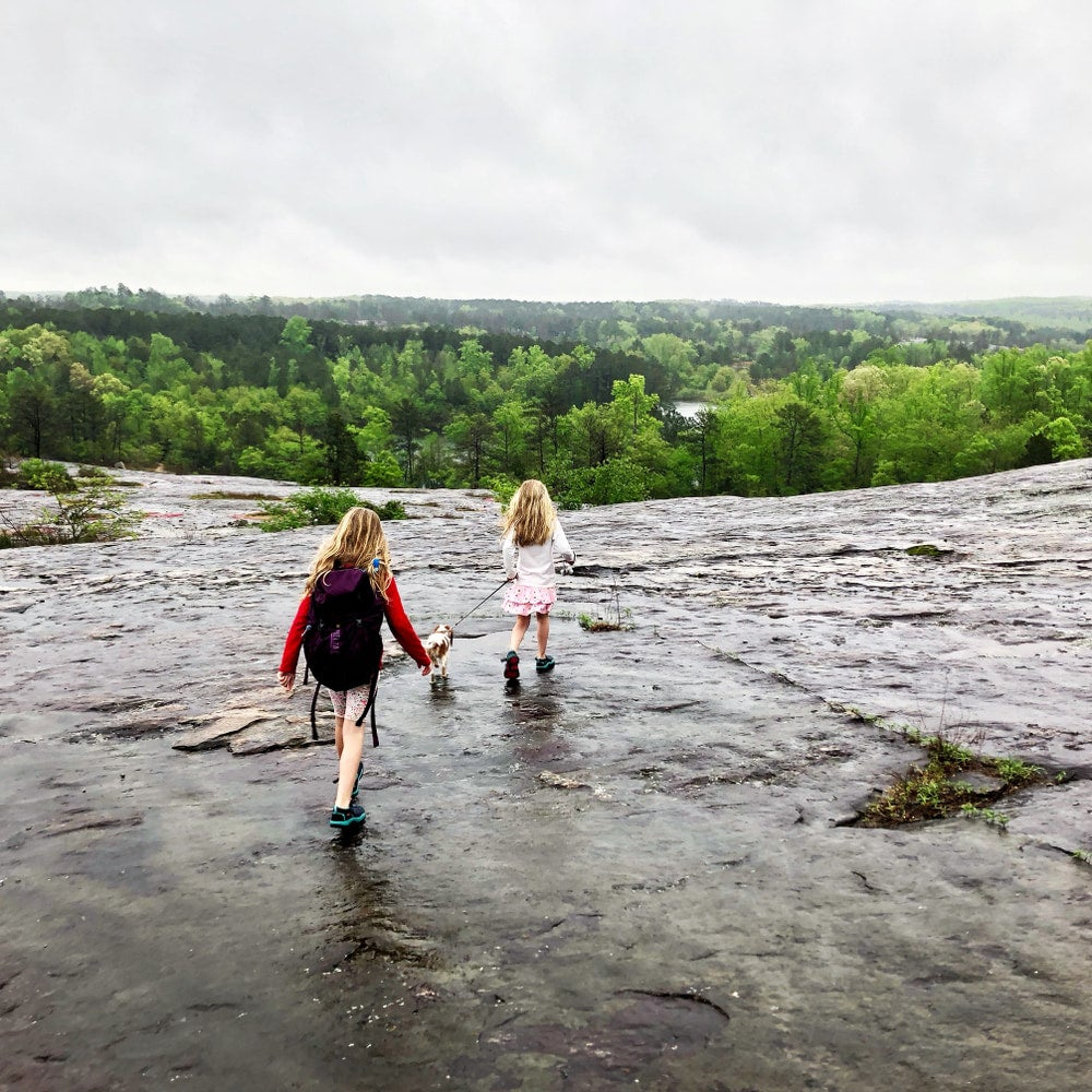 two children walking a dog on a wet granite outcropping on arabia mountain