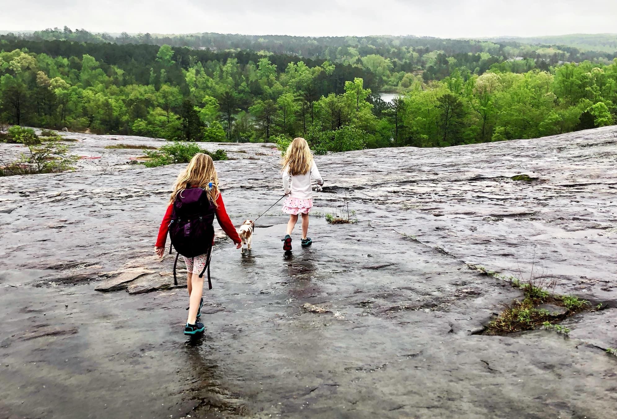 two children walking a dog on wet granite on arabia mountain