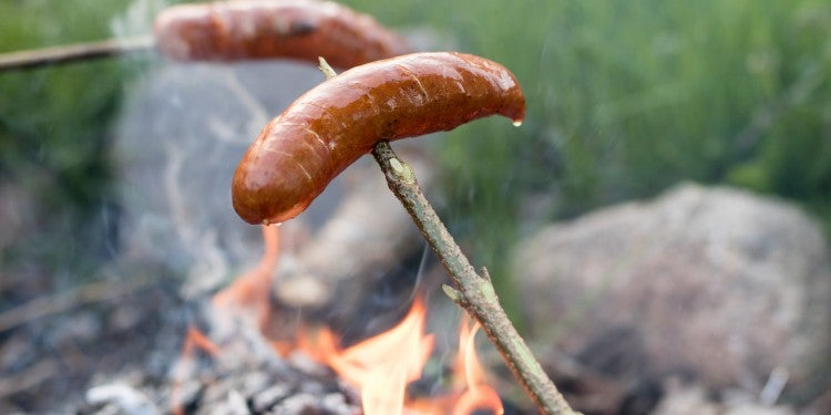 Roasting bratwursts over a fire.