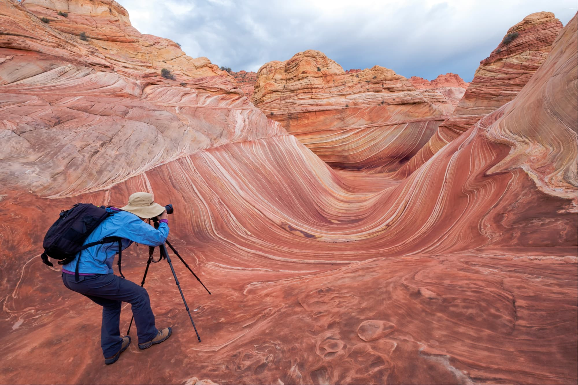 a man sets up a campera on a tripod to take a whoto of the wave rock formation in utah