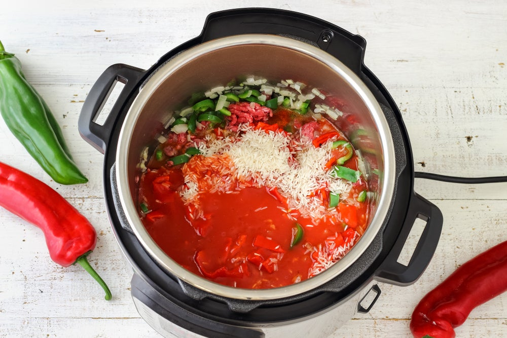 Instant pot with tomatoes, rice, and peppers inside