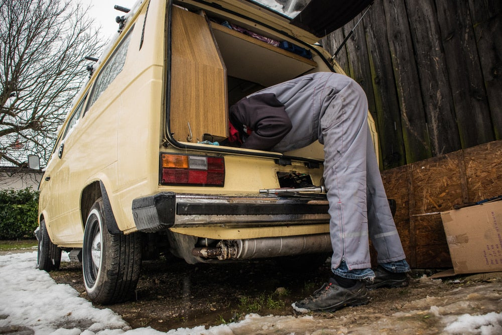 a man reaching into an RV van to repair the vehicle