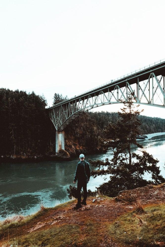Man standing beside Pass Lake under an iron bridge.