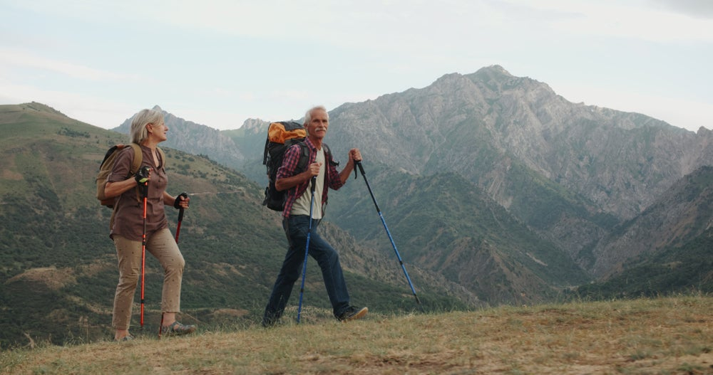 a retired couple hiking on a trail with mountains in the background