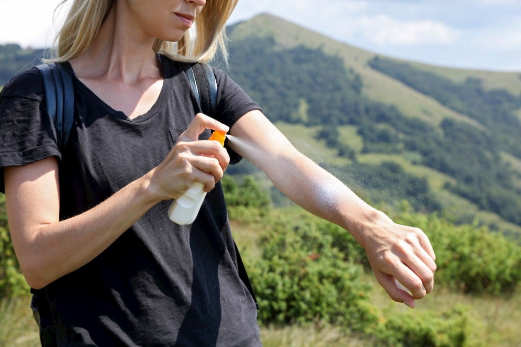 Woman applying spray sunscreen to arm on a hiking trail