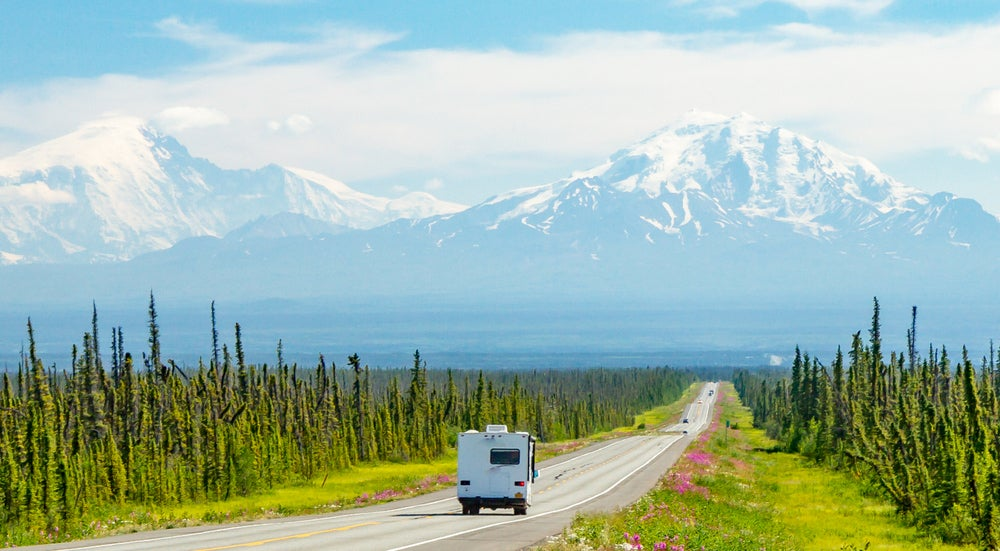 RV driving toward snow-capped mountains on a scenic road