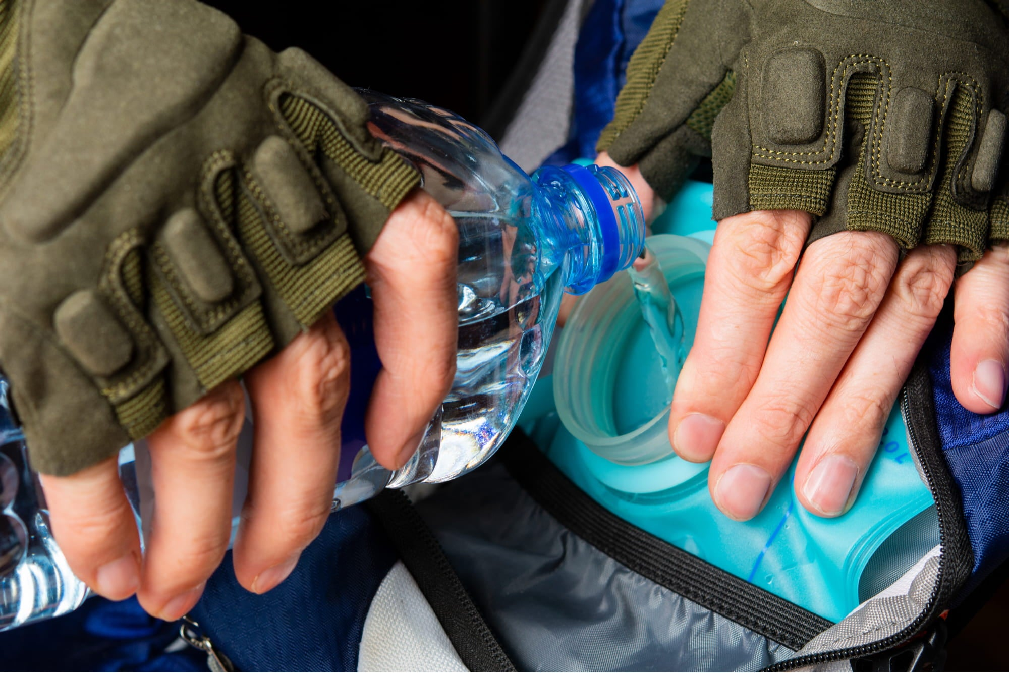 a pair of hands pouring water from a plastic bottle into a water bladder