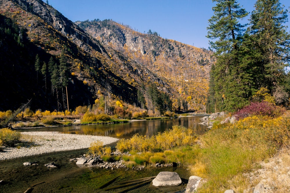Autumn foliage in the Wenatchee River winding through the mountains.