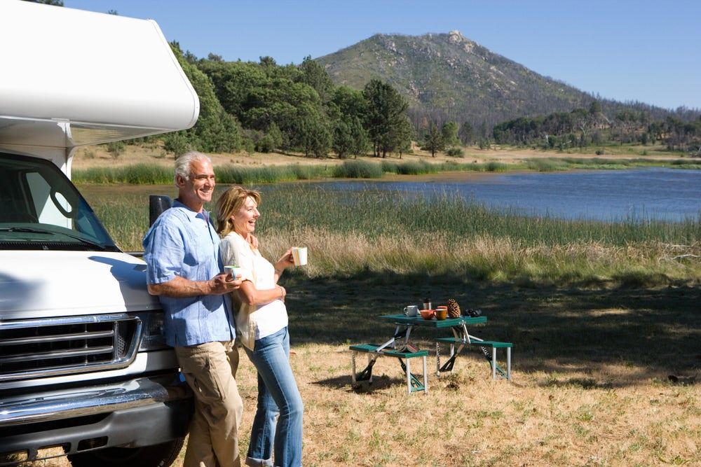 an elderly couple smiling next to a lake and leaning on their RV camper