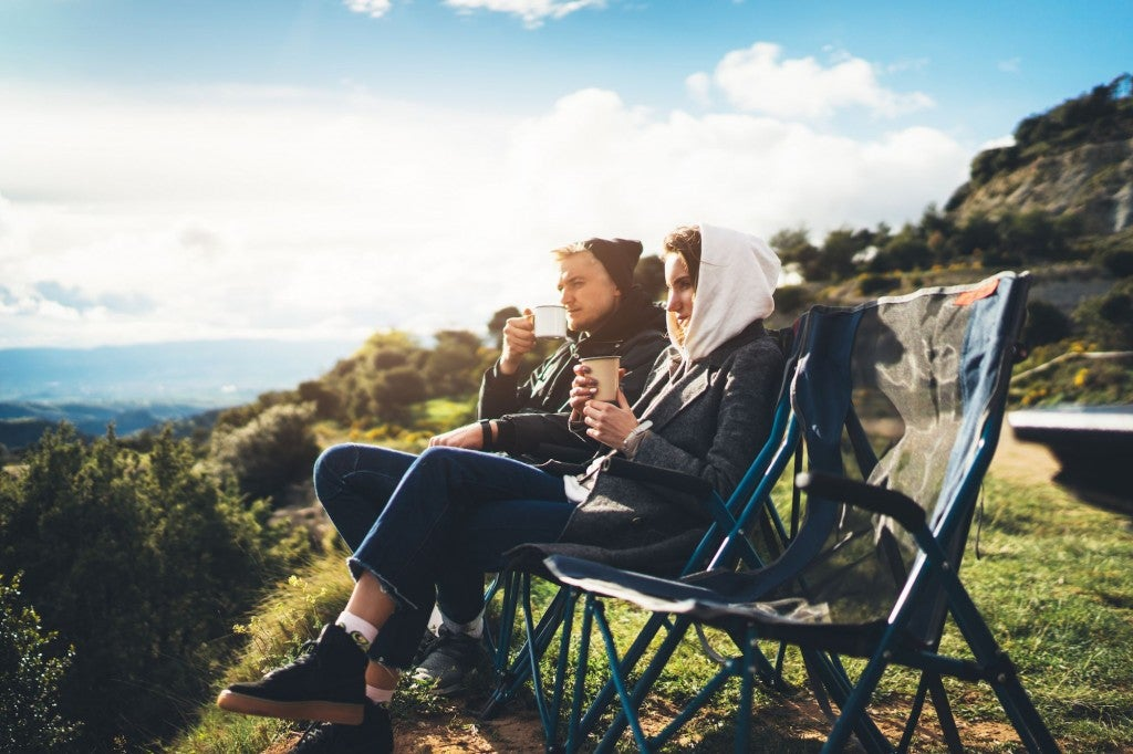 couple looking out over a tree-lined cliffside drinking coffee in their camping chairs