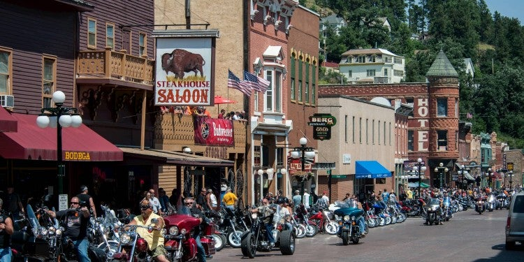 People on motorcycles next to buildings during sturgis motorcycle rally