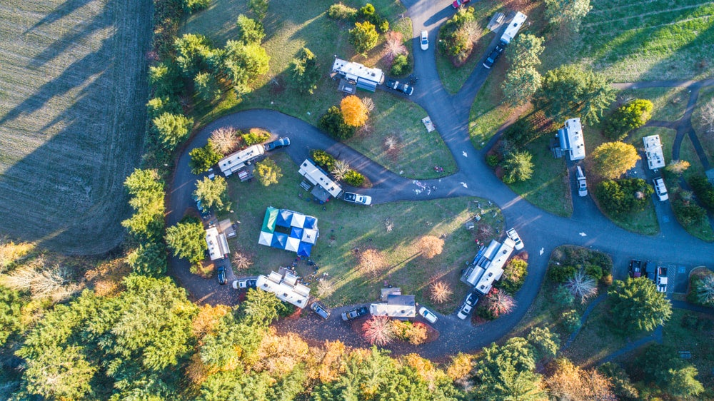 an ariel view of a campground loop with buildings, tents and RVs
