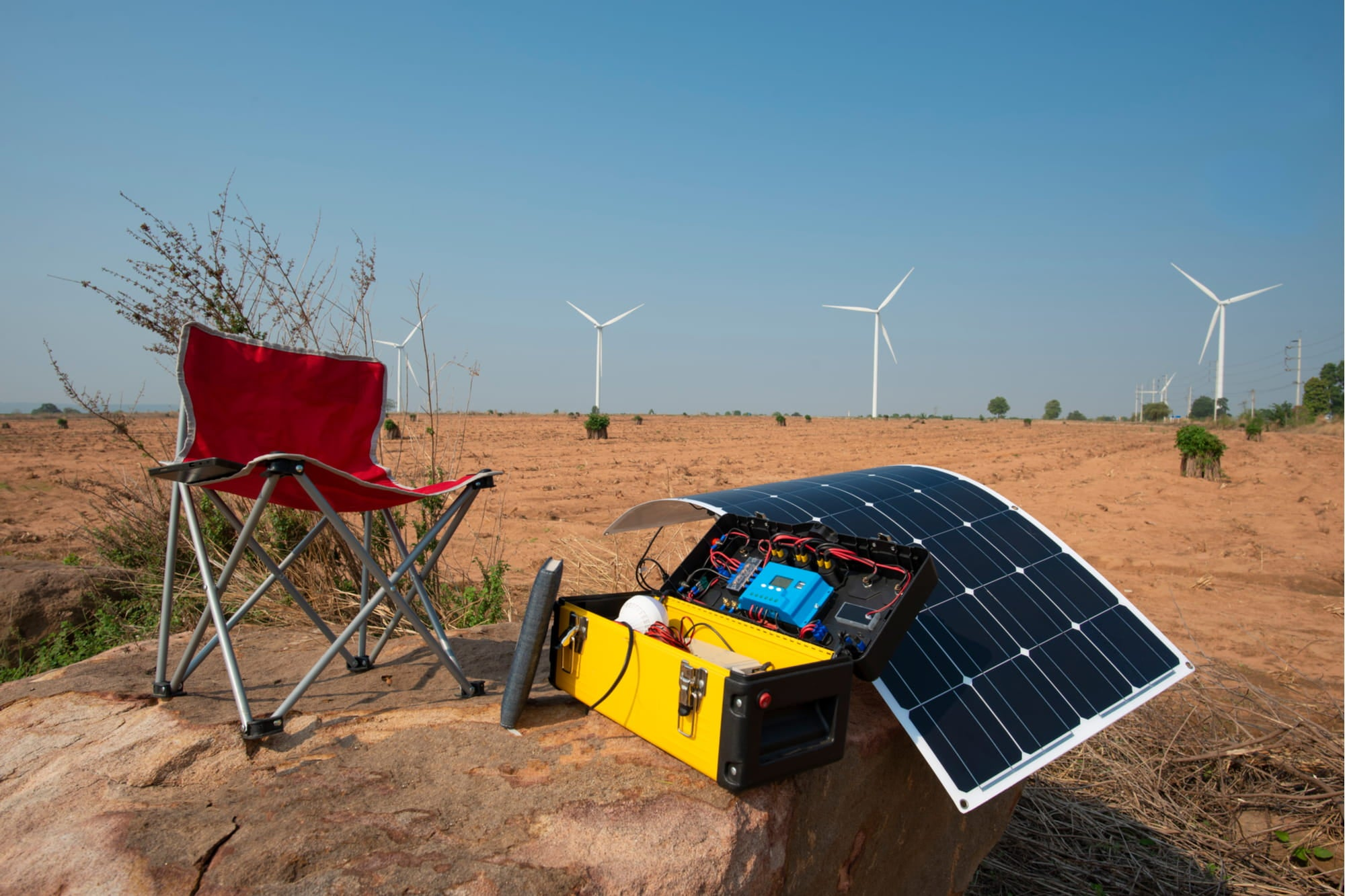 a chair next to a solar generator in a desert near wind turbines