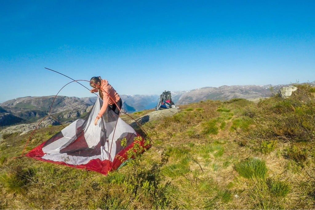 a woman struggling to set up a tent on a bald near a cliff