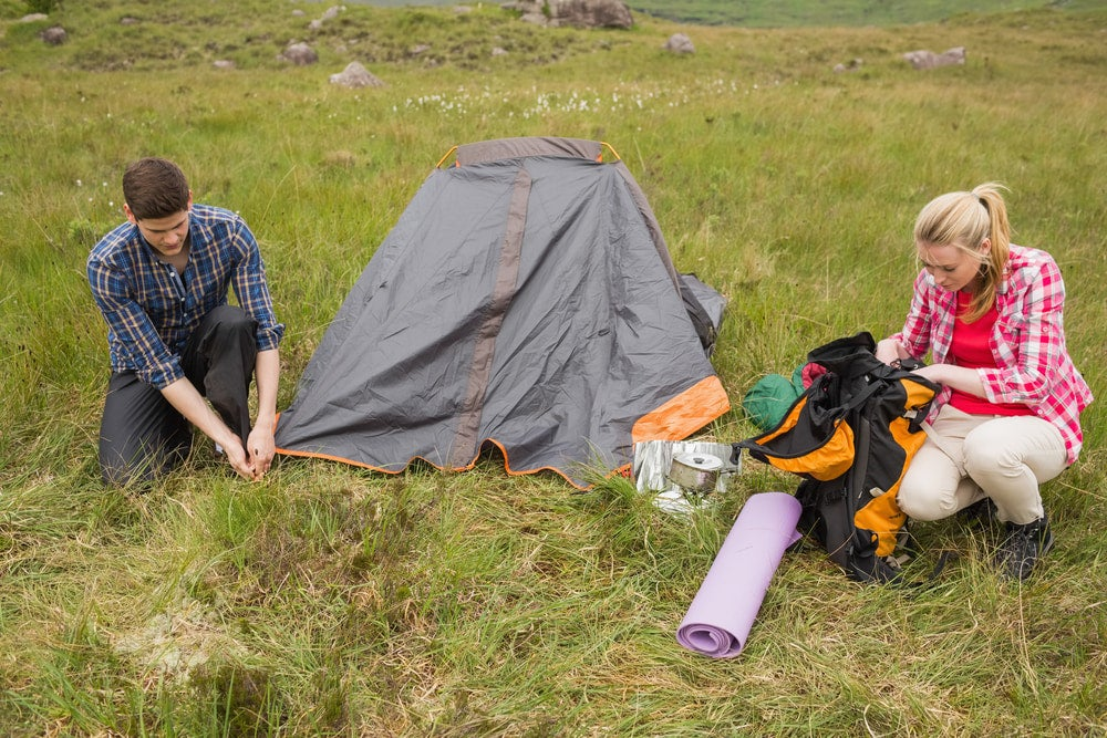 a man and a woman set up a tent and campsite on their first time camping