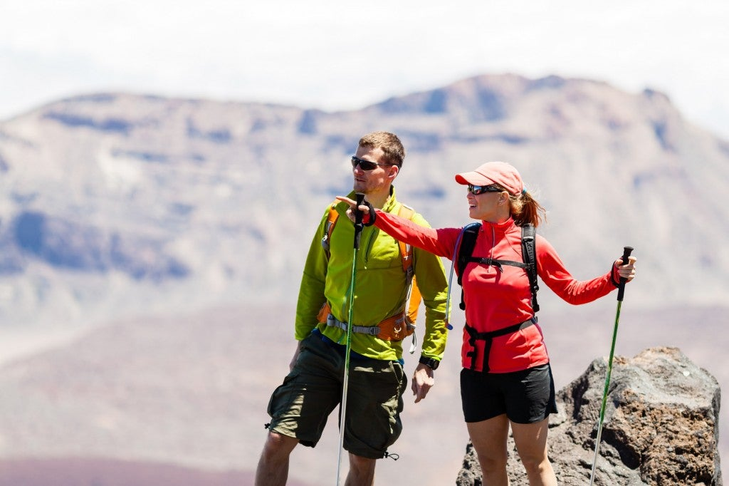 a couple wearing summer hiking outfits looks out on a hiking trail