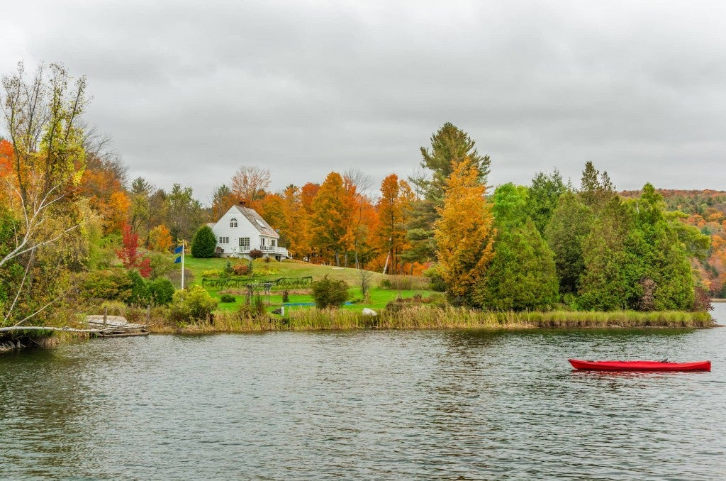 Panoramic view of fall trees, a lake, and a red canoe on the water.