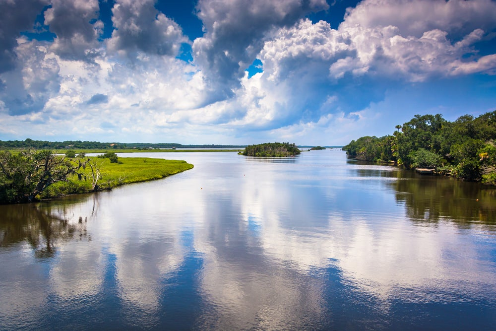 reflections of clouds on the tomoka river in tomoka state park in florida