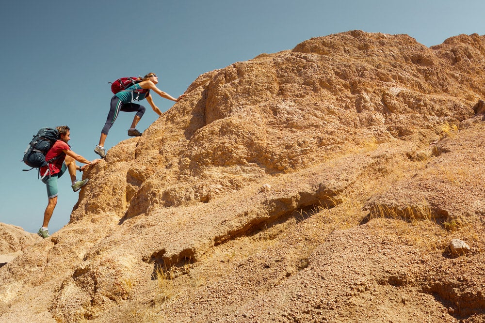 two hikers climbing orange rocks in the desert