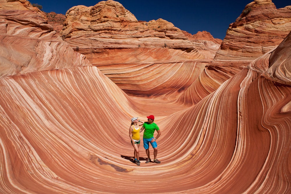 a young couple hiking stands in front of the wave in utah's coyote canyon north