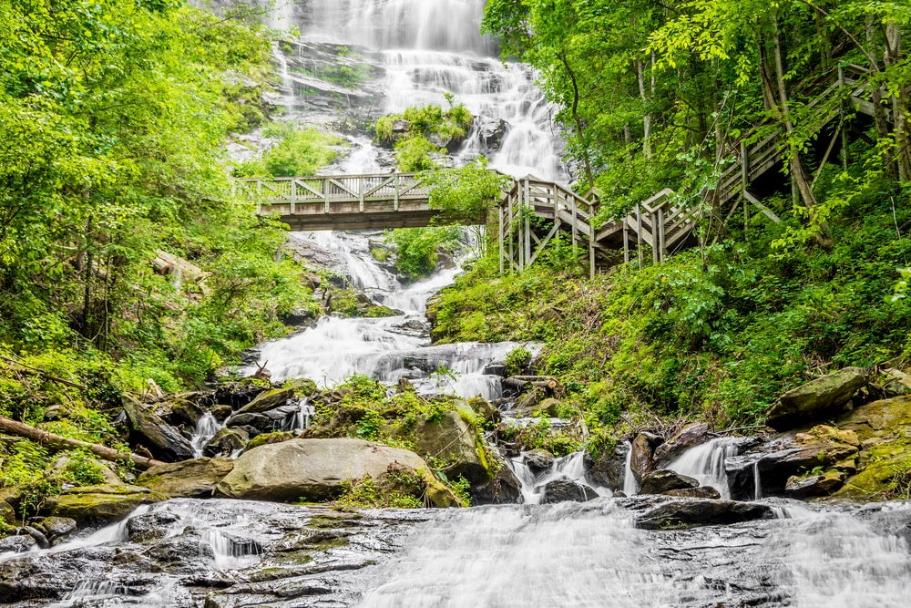 trees surround wooden bridge that crosses rocky waterfalls in amicalola falls state park