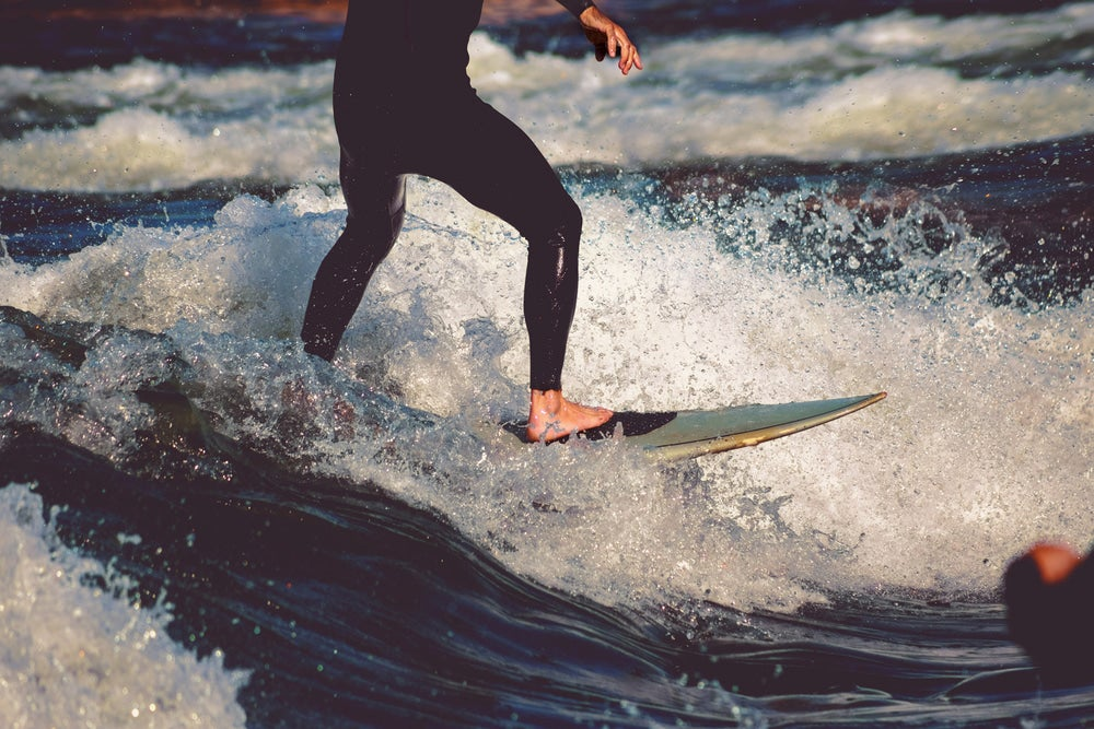 Surfer riding a breaking wave in a river.