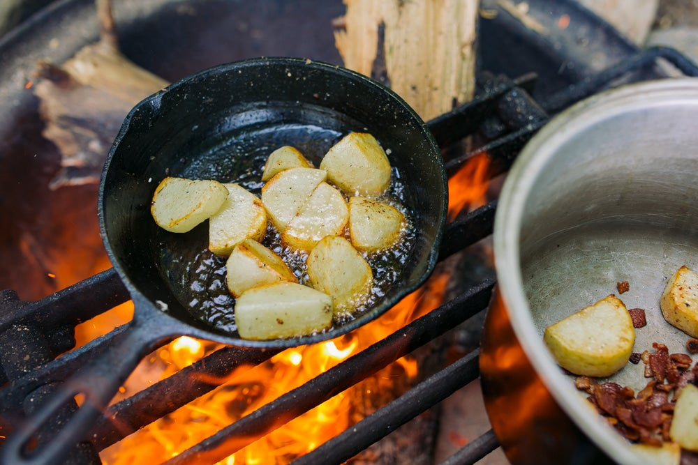 a pan cooking potatoes over an open fire at a campsite