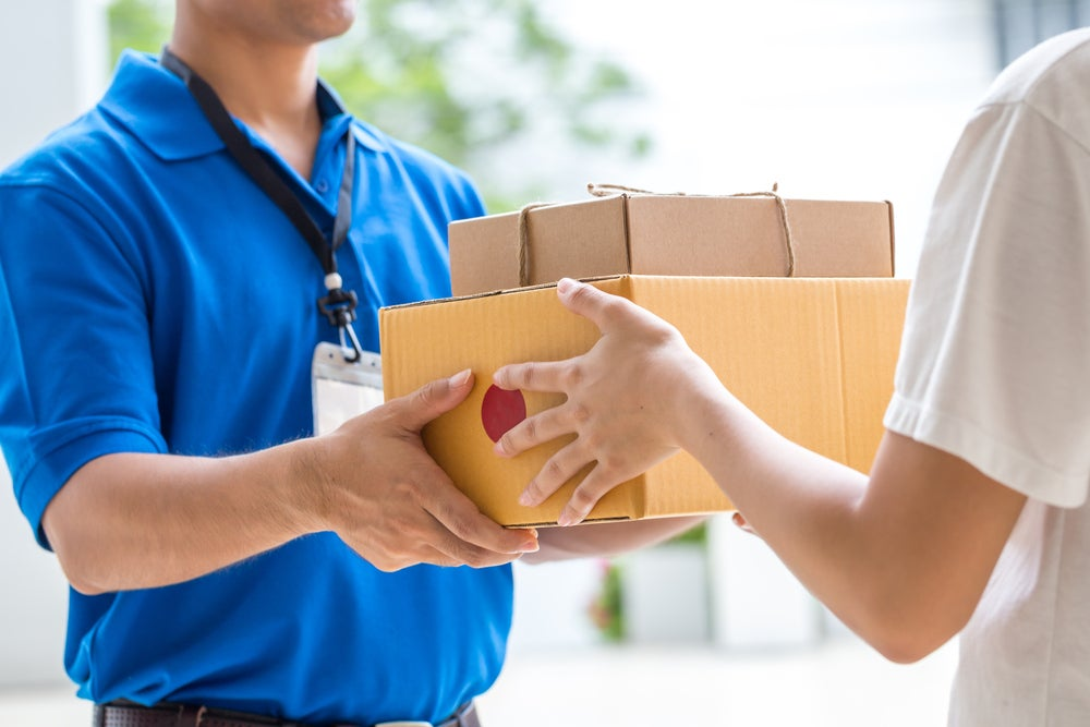 a postal worker handing a woman mail forwarded from elsewhere