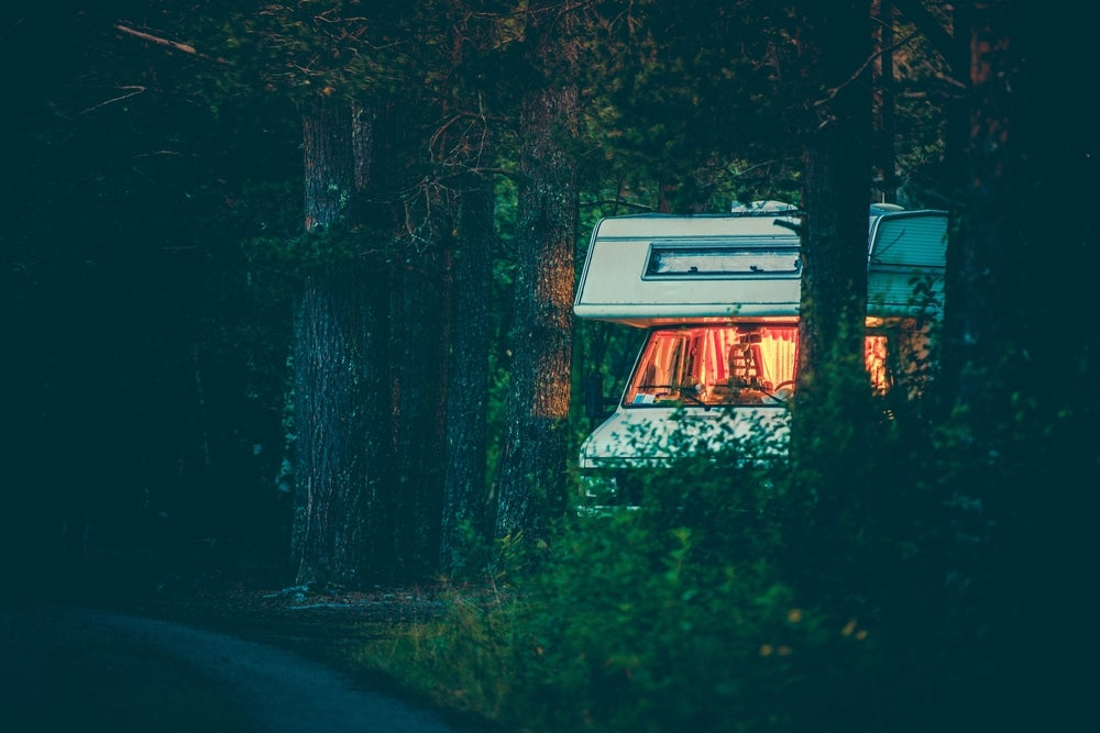an RV nestled into the forest while boondocking at night