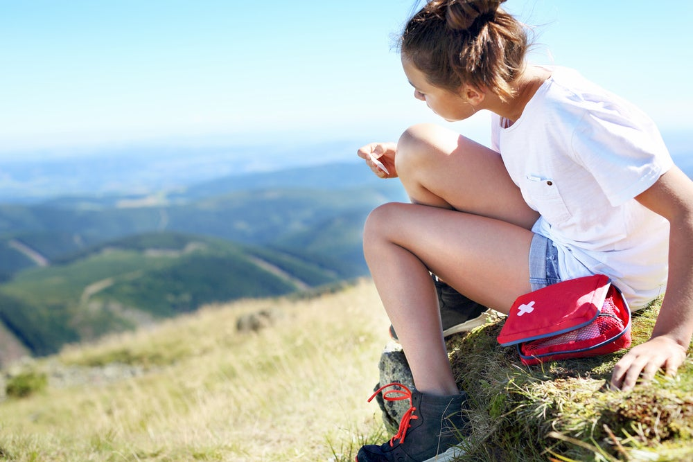Woman cleaning her knee with first aid kit and mountains in background